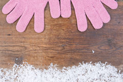 Wooden background with pink mittens winter snow on the border an Stock Photos