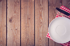 Wooden background with plate and silverware. View from above. Wooden background with plate and silverware Royalty Free Stock Images