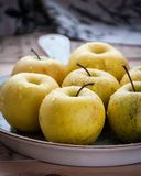 On a wooden background on a platter fresh apples with water droplets.  Royalty Free Stock Photography