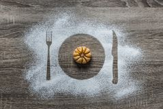 On a wooden background with powdered powder snow covered with silhouette a plate fork knife appliances lies mandarin orange Royalty Free Stock Images