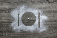 Wooden background with powdered powder snow covered with a silhouette a plate fork knife appliances is a white round tablet. On a wooden background with powdered Stock Photography