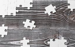 Wooden background with puzzles. Incomplete wooden puzzles on wooden desk, top view, flat lay. The concept of logical thinking, conundrum Stock Image