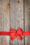 Wooden background with red bow and ribbon Stock Image