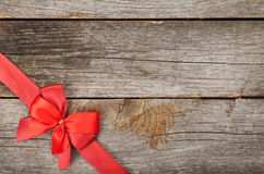Wooden background with red bow and ribbon Royalty Free Stock Photo