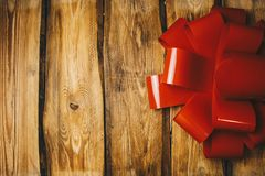 Wooden background with red bow and ribbon with copy space close up royalty free stock image