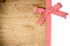 Wooden background with a red checkered ribbon Stock Image