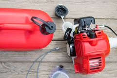 On a wooden background, a red lawnmower with an open gas tank, for refueling stock photo