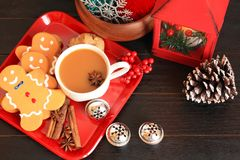 Above photo of three gingerbread men and coffee with star anise. Wooden background with red plate with tree gingerbread men a mug of coffee. Inside the coffee stock images