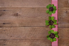 Wooden background with red and white checkered ribbon and green Royalty Free Stock Photos