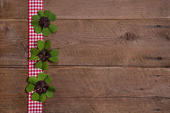 Wooden background with red and white checkered ribbon and green. Clovers for a happy new year Royalty Free Stock Photo