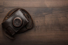 Wooden background with retro still camera Stock Photos