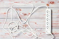 . wooden background in retro style, on it is an extension cord with European cuts. Wooden background in retro style, on it is an extension cord with European stock photos