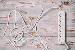 . wooden background in retro style, on it is an extension cord with European cuts. Wooden background in retro style, on it is an extension cord with European stock image