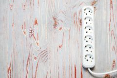 . wooden background in retro style, on it is an extension cord with European cuts. Wooden background in retro style, on it is an extension cord with European royalty free stock photography