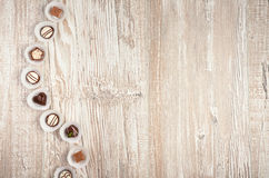 Wooden background with a row of chocolates, space Royalty Free Stock Image