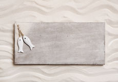 Wooden background with sand and two fishes on an sign like a mes Stock Photo