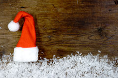 Wooden background with santa cap, snow on the border and copyspa Stock Image