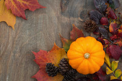 Wooden background with seasonal pumpkin and leaves, top view Royalty Free Stock Photos