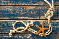 Wooden background with starfish and marine rope Stock Images