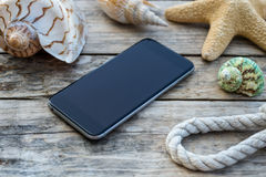 Wooden background with starfish, phone and shell Royalty Free Stock Image