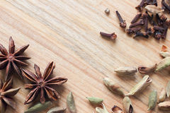 Wooden background texture with aromatic spices. Royalty Free Stock Photo
