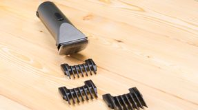 Wooden background there is an electric hair clipper and a set of nozzles to it. On a wooden background there is an electric hair clipper and a set of nozzles to stock photo