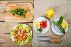 On a wooden background there are knives, a cutting board with greens plates with vegetables. View from above Royalty Free Stock Images
