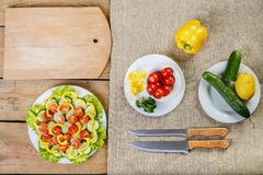 On a wooden background there are knives, a plate with salad, cucumber, tomato and pepper. View from above Stock Photos