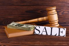 Auctioneer`s hammer, a notepad on which a stack of dollar bills and a sign with an inscription on sale. On a wooden background there is a wooden auctioneer`s Stock Image