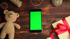 Wooden background. Top view. Black smartphone with green screen lying on the table with christmas holiday decoration. stock footage