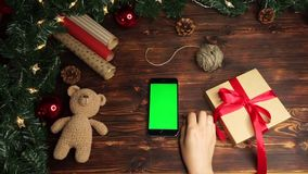 Wooden background. Top view. Black smartphone with green screen lying on the table with christmas holiday decoration. Wooden background. Top view. Black stock footage