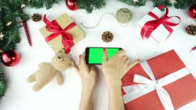 Wooden background. Top view. Black smartphone with green screen lying on the table with christmas holiday decoration. Wooden background. Top view. Black stock video footage