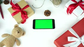 Wooden background. Top view. Black smartphone with green screen lying on the table with christmas holiday decoration. Wooden background. Top view. Black stock video