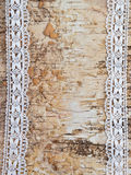 Wooden background with white lace. Wooden birch background with white lace border royalty free stock photography