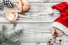 Wooden background. White. Winter card. Mandarins. Pinecone. His Santa`s hat. the fir tree. Space for greeting card with Christmas Royalty Free Stock Photos
