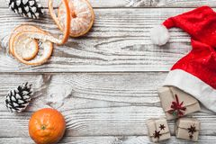 Wooden background. White. Winter card. Mandarins. Pinecone. His Santa`s hat. Space for greeting card with Christmas or New Year. Stock Photo
