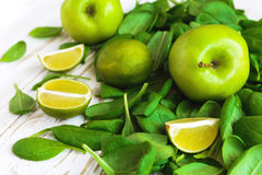 Wooden backgroung with healthy green spinach, lime and apple. Healthy food concept Royalty Free Stock Photography
