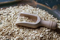 Wooden bailer with oat flakes royalty free stock photo