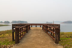Wooden balcony on the lake that covering by morning fog Royalty Free Stock Images