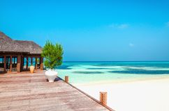 Wooden balcony of a luxurious resort with a view of a paradise beach with tall palm trees. With blue sky Stock Image