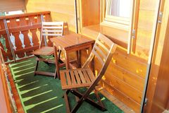 Balcony. Wooden balcony of mountain house with table and two chairs Stock Photo
