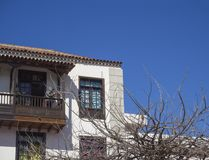 Wooden balcony typical on traditional house in colonial style in. Canary islands, Tenerife with bare tree branches and blue sky background Royalty Free Stock Image