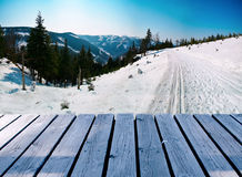 Wooden balcony on winter landscape with skiing path Royalty Free Stock Photos