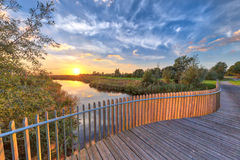 Wooden Balustrade balcony on bridge. Bright sunset over Wooden Balustrade balcony on bridge in Onlanden Nature reserve waterlogging area Groningen, Netherlands Royalty Free Stock Photo