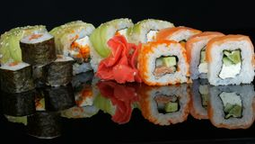 Wooden bamboo Chinese chopsticks put colored sushi rolls and ginger on a mirror surface against a black background
