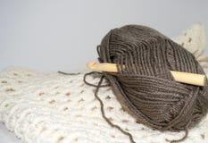 Wooden bamboo crochet hook in bundle of  yarn. Large wooden bamboo crochet hook in skein of brown yarn atop off-white (ecru) crocheted fabric Royalty Free Stock Image