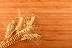 Wooden bamboo cutting board with nine wheat ears Royalty Free Stock Photos