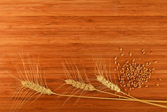 Wooden bamboo cutting board with three wheat ears and grains Royalty Free Stock Photo
