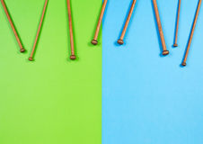 Wooden bamboo knitting needles arranged as frame border on colorful background Stock Images