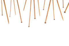 Wooden bamboo knitting needles arranged as frame border on white background. Top view. Copy space for text stock photo
